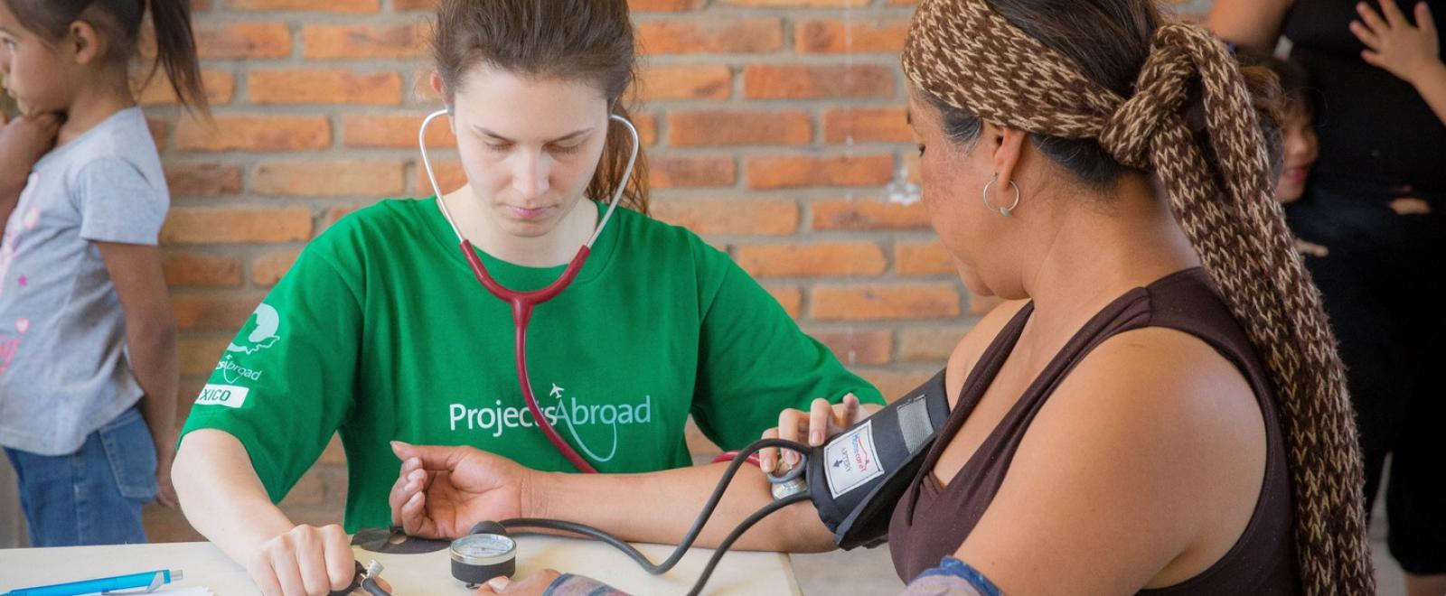 A Projects Abroad volunteer at her Spring Break Public Health placement checking the blood pressure of a local woman